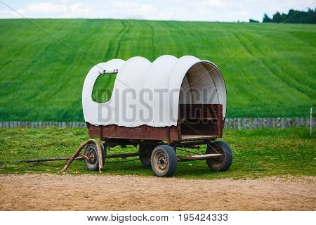 Old covered wagon with white top against green grass field background.