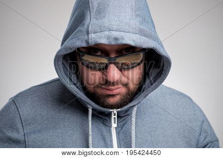 A mysterious bearded man in sunglasses hid under a hood. He looks suspiciously at you.