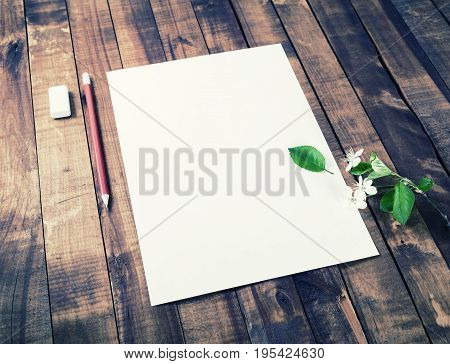 Blank letterhead pencil eraser flowers and green leaves on vintage wood background. Bank stationery template. Mock up for placing your design.