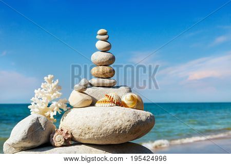 Rock zen of white stones shells and coral on a background of the summer sea and blue sky. Concept of harmony and balance.