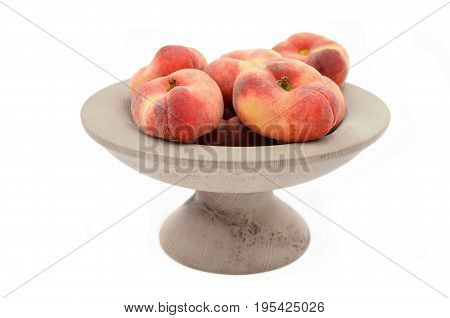 peach in bowl on white background close up