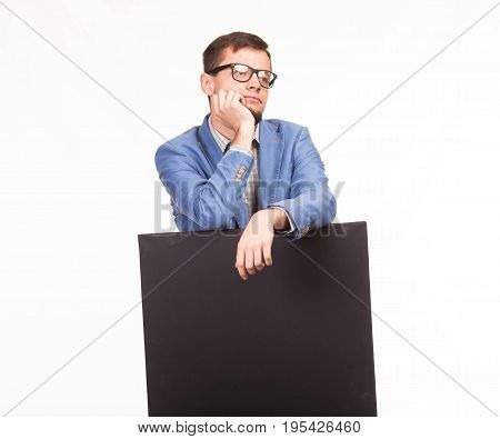 Young thoughtful man portrait of a confident businessman showing presentation, pointing placard gray background. Ideal for banners, registration forms, presentation, landings, presenting concept.
