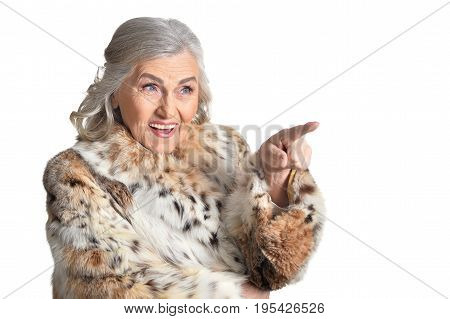Senior woman in fur point the finger on something behind the frame on white background
