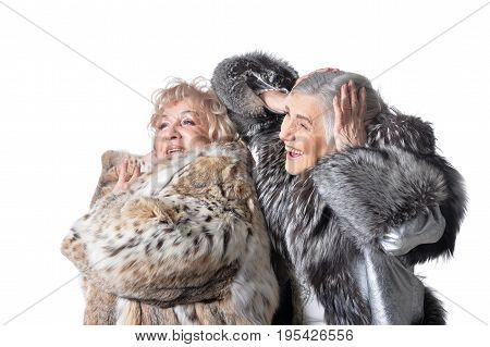 Two senior women dancing on white background