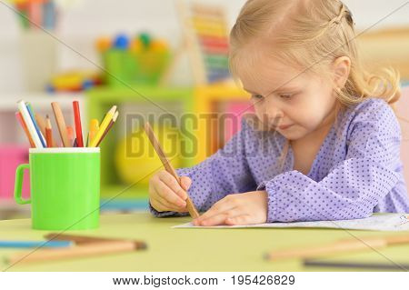 Cute little girl drawing with pencil in childrens room