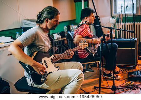 Behind the scene. Rock band practice in the messy recording music studio. Alternative musician group live playing