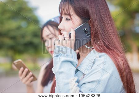 Beautiful Asian woman with friend using and looking at smart phone.