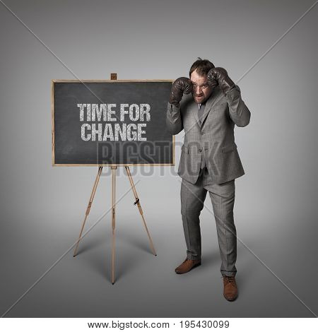 Time for change text on blackboard with businessman with boxing gloves