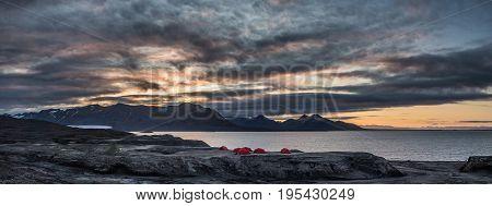 Midnight sun at campsite near a glacier coast Svalbard