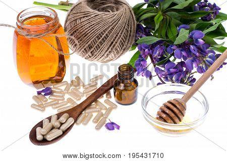 Medicinal herbs, honey,  natural capsules and pills in medicine.