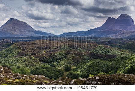 Assynt Peninsula Scotland - June 7 2012: Wild green and brown land seen from B869 near Achmelvich shows old mountain peaks under heavy gray and dark cloudscape.