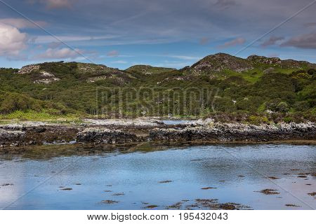 Assynt Peninsula Scotland - June 7 2012: Green rough hills and blue Atlantic Ocean waters of inlet South of Loch An Arbhair. Blue cloudy sky.