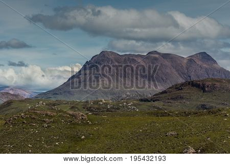 Assynt Peninsula Scotland - June 7 2012: Brown mountain ridge under blue skies with white and gray clouds fronted by green wild rough slopes east of Loch Buine Moire.