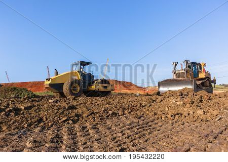 Construction industrial earthworks dozer and compactor machines leveling sand stones closeup abstract.