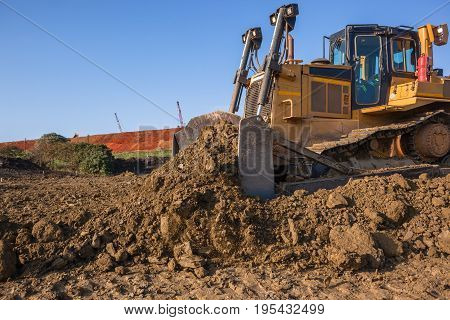 Construction industrial earth mover dozer machine scoop bucket moving sand stones closeup abstract.