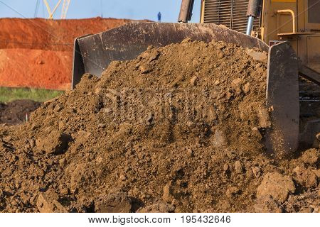 Construction industrial earthworks earth mover dozer machine scoop bucket moving sand stones closeup abstract.