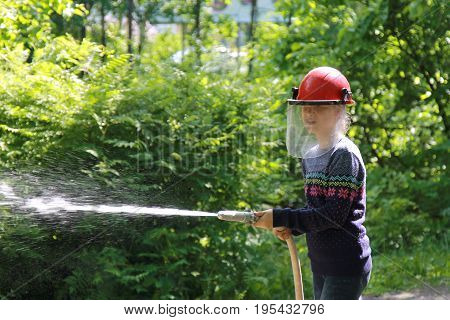 Teenager learning the firefighter profession. The girl in fire helmet pours water from the hose. Educational program for kids