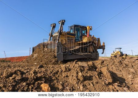 Construction industrial earthworks earth mover dozer machine leveling sand stones closeup abstract.