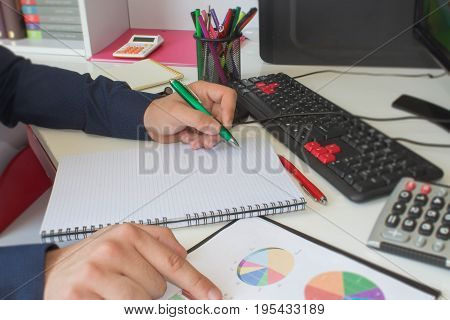 man writing notes from computer on wooden table. Man hand with pen calculator and computer on wooden table