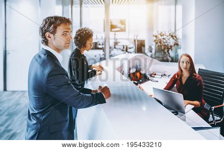Handsome caucasian businessman in formal suit and his black colleague with afro hair tired while standing near reception and trying register for business meeting but woman with laptop asking to wait