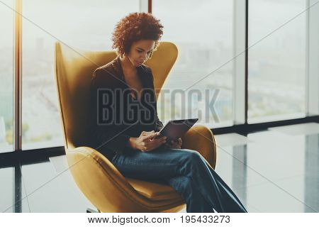 Young cute Brazilian probationer using digital tablet to prepare for interview while sitting in yellow armchair pensive afro american girl working on digital pad in office settings near huge window