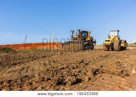Construction industrial earthworks earth mover dozer and compactor machines leveling earth soil.