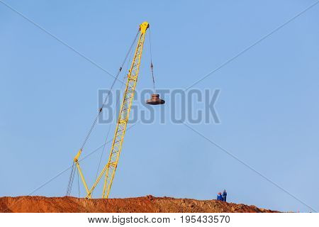 Construction industrial earthworks crane dropping compactor landscape.