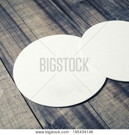 Two blank white beer coasters on vintage wood table background. Responsive design mockup.