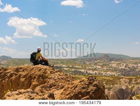 Sporty woman hiker on top of rock mountain