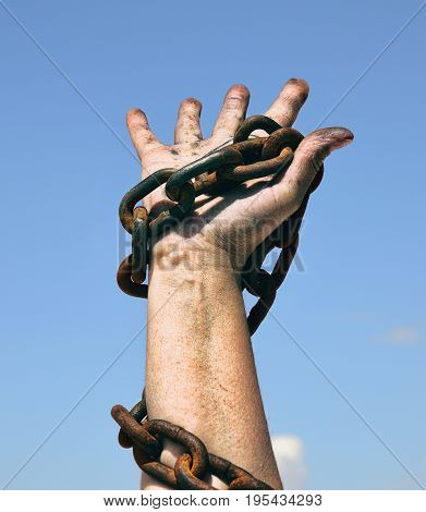 right female hand holds a rusty chain against the blue sky