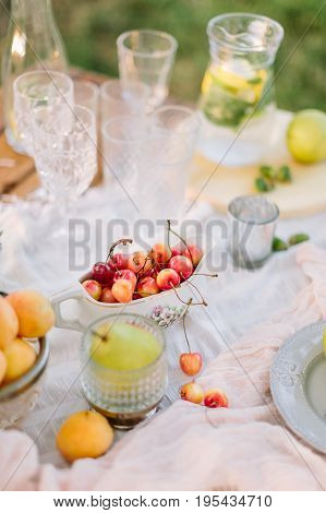 picnic, lifestyle, vegetarianism, celebration, wedding concept - still-life with tableware: plates, crystal globes, gravy boat full of cherries and jug of lemonade