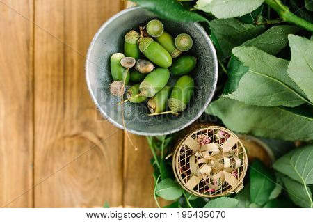 environment, nature, countrylife concept - flat-lay of little bowl with fresh green acorns, leaves of rose bushes and small cardboard gift box with pink dried flowers on wooden table