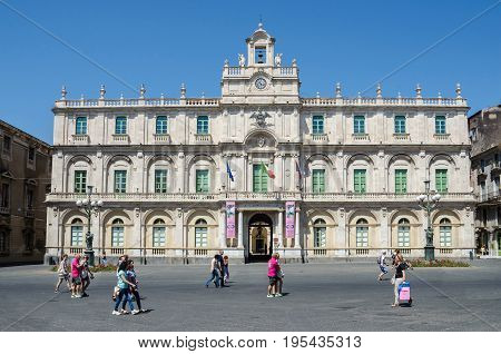 Catania Italy - July 3 2017: Historical building of the University the oldest university in Sicily with many people walking through the place. Its academic nickname Siculorum Gymnasium is to be seen over the entrance.
