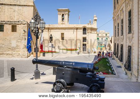 View of the Castille Place from the Main Door of the Auberge de Castile et Leon toward Our Lady of Victories Chapel with the canon and the Monument of Prime Minister Boffa in Valletta Malta