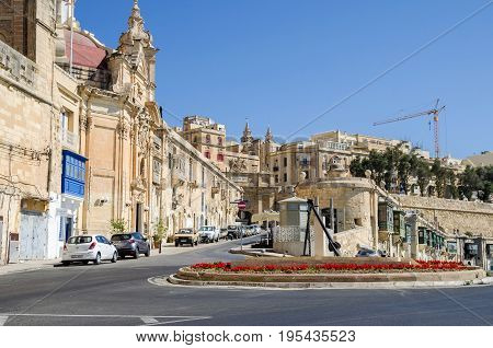 Valletta Malta - June 4 2017: The view along the Liesse with the baroque Church of Our Lady of Liesse and Victoria Gate near the shores of the Grand Harbour.
