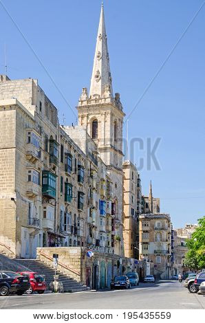 Valletta Malta - June 4 2017: Marsamxett Street with the landmark tower of the St.Paul's Anglican Pro-Cathedral constructed with Maltese limestone in a neo-classical style and residential buildings with typical colorful balconies