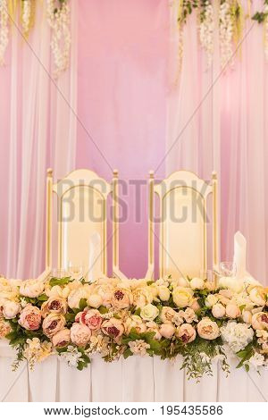 festive table for the bride and groom decorated with pink cloth and flowers. Wedding table decor concept.