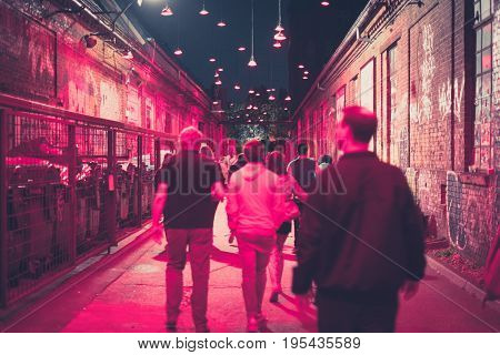 People Walking On Street At Night In Nightlife Area - Blurred