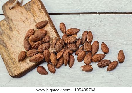 many peeled almonds on a wooden background