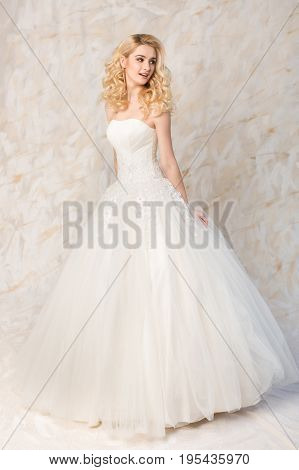 fashionable white gown, beautiful blonde model, bride hairstyle and makeup concept - young smiling girl in wedding festive dress, standing indoors on light background, slender woman look sideways