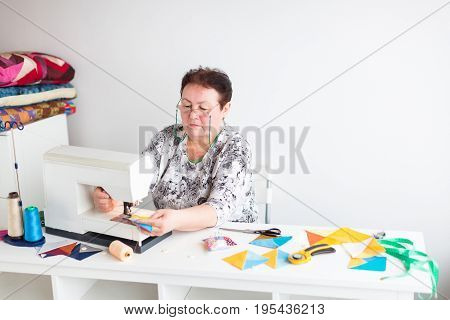 patchwork and quilting in the workshop of a tailor woman on white background - tailor hands sew on sewing machine scraps of blue and yellow fabric for patchwork