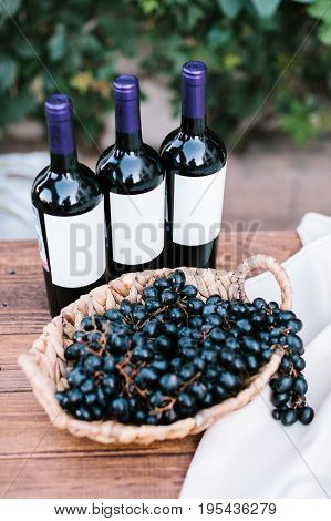 three bottles of red wine and cluster of labruscan grapes in a wattled plate on a wooden table, outdoor. aperitif at a wedding party.