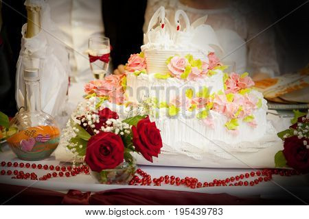 Wedding still life. A large beautiful cake, decorated with roses from cream and swans.