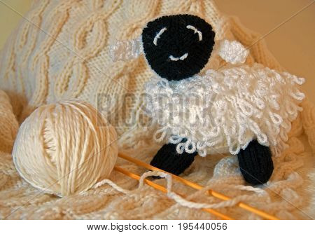 A photo of a hand-knitted white baby blanket along with a hand-knitted curly lamb