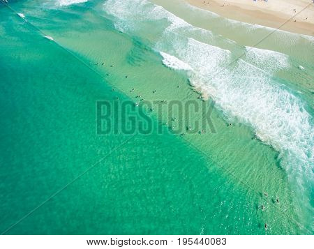 An aerial photo of Surfers waiting for a wave in clear blue water on the Gold Coast