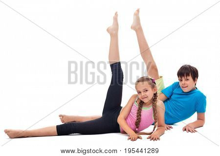 Kids doing gymnastic exercise lying on the floor and rising legs - isolated