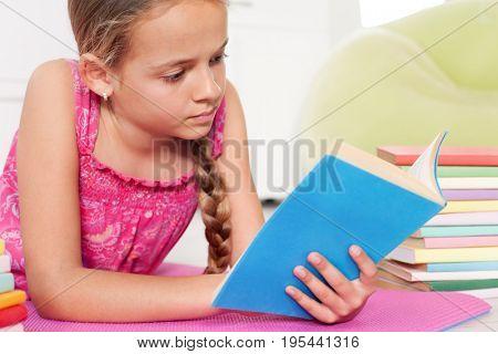 Girl reading on the floor, lying among stacks of books