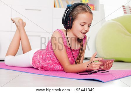 Young girl using her phone listening to music lying on the floor at home
