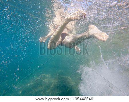 Snorkelling woman in bikini kicks up bubbles underwater