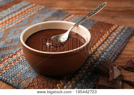 Bowl with delicious melted chocolate sauce and spoon on table